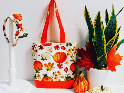 A cloth bag with a pumpkins and Fall flowers theme fabric. A head-band hangs beside it made of the same fabric.