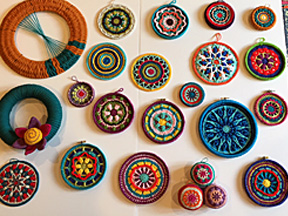 Crocheted and woven wall art using hand-spun yarn into round designs.