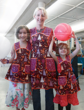 A mother with two daughters are modeling matching aprons.