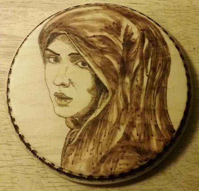 intricate woodburning sketch of woman's face