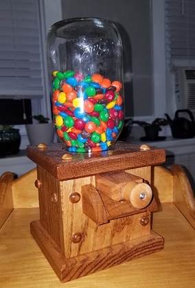 A glass jug, filled with small candies, sits atop a small wooden holder to be used for dispensing the candies one by one, just like usual jelly-bean candy dispensers.