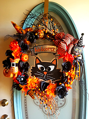 Front door wreath featuring a cartoon Halloween cat.