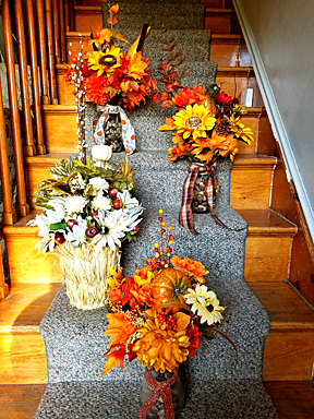 Four baskets of silk flowers shown on a staircase.