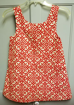 A little dress for a girl about size 3.  White with red mosaic designs in a straight A-line style.