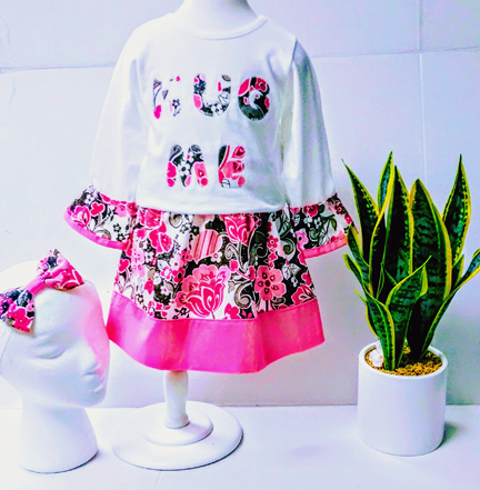 "A girl's coordinated outfit, with the top having the words, ""Hug me"" using the same fabric as the skirt. A matching head-band bow is also shown."
