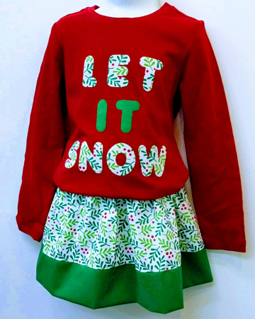 "A girl's coordinated outfit showing a red top with the words ""Let it snow!"" in fabric lettering that matches the green and red skirt below. Very sophisticated looking!"