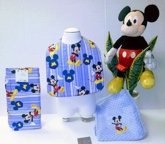 Baby's matching fabric set of a bib, blanket, changing pad and mitt. All in a Mickey Mouse print.