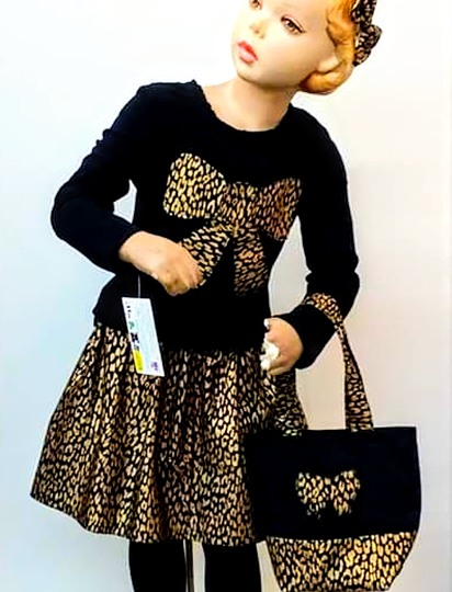 Very sophisticated coordinated outfit. There is a black top, typical of ballet tops, with a print bow which matches the printed skirt, and the bag the mannekin holds.