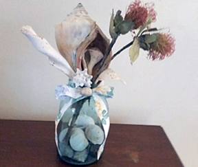 Shown is a single glass vase with stones inside, holding silk flowers.