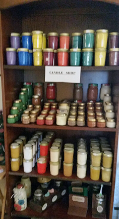 "This is a ""candle shop"" display on a vertical shelving cabinet. There are many jars with colorful waxes shown."