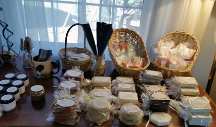 A desktop in front of a home window shows many wrapped soaps and bath salves.