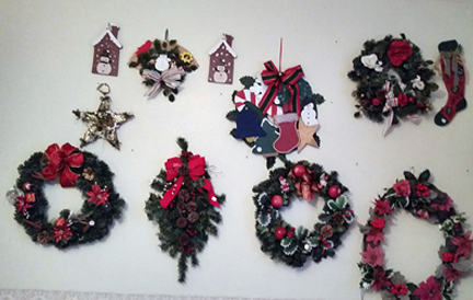 Wall displays:  six litttle wreaths using artificial coniferous branches and red ribbons and balls. Also flat wall or door hangings, like a snowman in front of a cartoo housefront, a star, a stocking...etc.