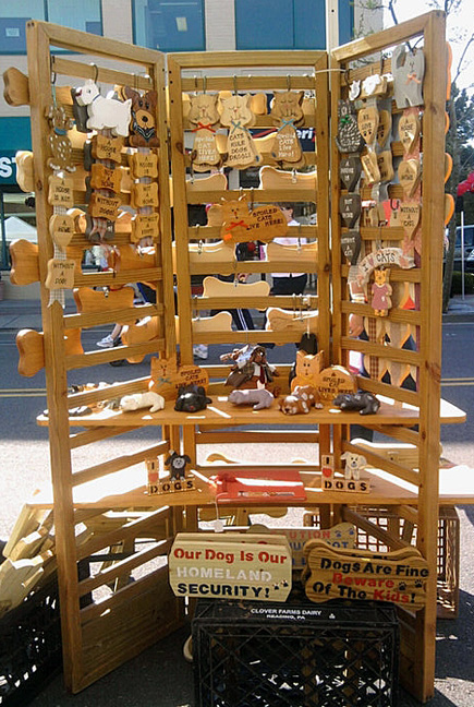 "On a wooden rack are numerous wooden signs, like ""The dogs are fine, beware the kids""."