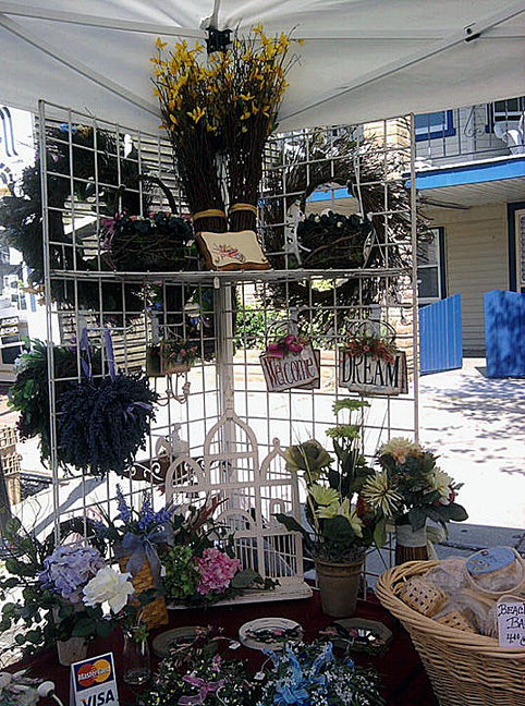 A stand-alone display with wreaths and silk florals, with other Colonial-style decorations, and wicker items.