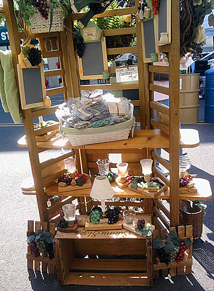 A vertical shelving unit holds many different items, most made of wood. There's also a wicker basket with a sewn-in lining, with various items in it for a gift basket. Candle holders, electric lights whose bulbs look like flames, etc., in Colonial artistry. 7 inch by 9 inch chalk boards for magnetic message boards, decorated with ribbons.