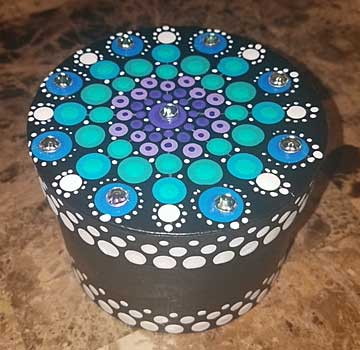 It is a round box about 2 1/2 inches tall perhaps, by 3 inches or so wide. covered in 2 shades of  turquoise dots among white and grey dots.