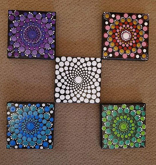 Five square tiles, covered with designs of dots laid out with one in the center and one in each corner.