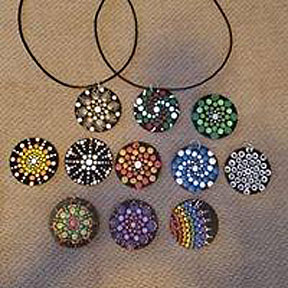 Eleven pendants, two with ties.  Each pendant appears to be 1 1/2 to 2 1/2 inches diameter. Each covered with dots in different color schemes and designs.