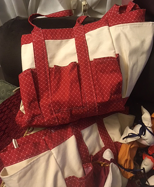 Two canvas bags with red-print trim and pockets.