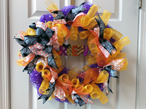 Wreath with Halloween theme, sing purple and gold netted ribbons in curly-Qs and swirls, with added blue ribbons, etc.