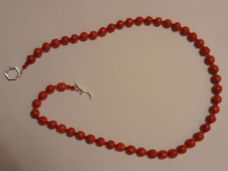 A string of blood-red round beads for a ladies necklace, approximately 18 inches. Clasp is the toggle through circle kind.