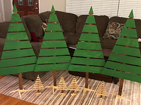 Four green-painted wooden slats on a vertical brown sturdy stick supported to stand as unadorned Christmas trees on stands, standing about 4.5 feet tall, plus 4 small trees, same as large, but about 8 inches tall, attheir feet.