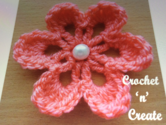 "A crocheted flower with a pearl button center with the words ""Crochet 'n' Create""."