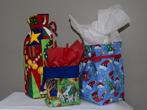 This photo shows three cloth bags, sewn into open-top bags with attached yarn ribbons.