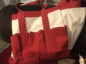 Multi-pockets on a canvas bag with red print pockets and trim.  Outside pockets could be for gardening tools.