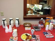 The serving table laden with food and breakfast beverages